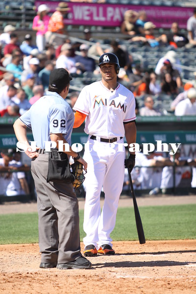 Giancarlo Stanton of the Miami Marlins talking with home plate umpire