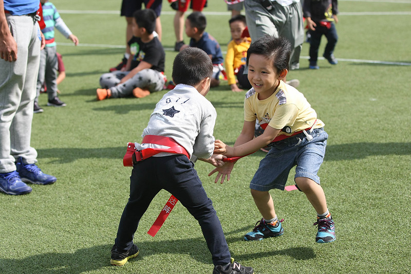 2014 NFL Home Field Shanghai - Week 4 - Participants of all ages take part in the team-building clinics where they experience and learn the basics of American football.