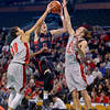 Central Catholic's Tyler Nelson (11) drives between Catholic Memorial defenders.