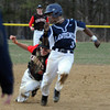 North Andover's short stop, captain Matthew Varoutsos tags out Lawrence's Elvis Peralta who is caught running between second and third base. 4/11/2014.