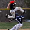 North Andover's short stop, captain Matthew Varoutsos leaps over Lawrence's Elvis Peralta after catching the high throw and managed to tag him out at second base.4/11/2014.