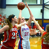 RYAN HUTTON/ Staff photo.  <br /> Londonderry's Taylor Collins (20) tries to put up a shot over the outreached arms of Pinkerton defenders Valarie Martin (25) and Colleen Fortier (23) during the third period of Thursday night's game.
