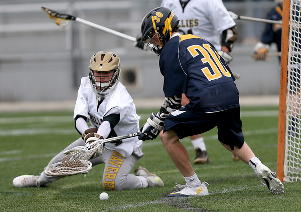 Haverhill goalie Zach Grundy lunges for a save as Andover's George Cardillo looks for a rebound.
