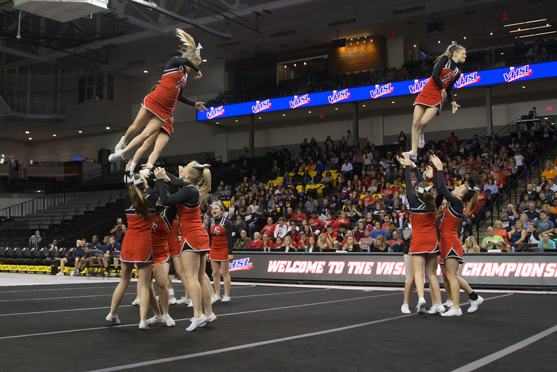 ERHS Cheer performing in round 1 at State Championships. Junior Left stunt group Junior Tori Cook twists coming down, right stunt group Freshman Savannah Baugher twists coming down out of a stunt.