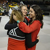 Seniors Brooke Trimble (front) and Alyssa Breeden (back) huge head Coach Farren Frances after coming off the mat from their final performance.