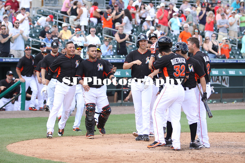 Miami Marlins players congratulate Derek Dietrich on his winning home run
