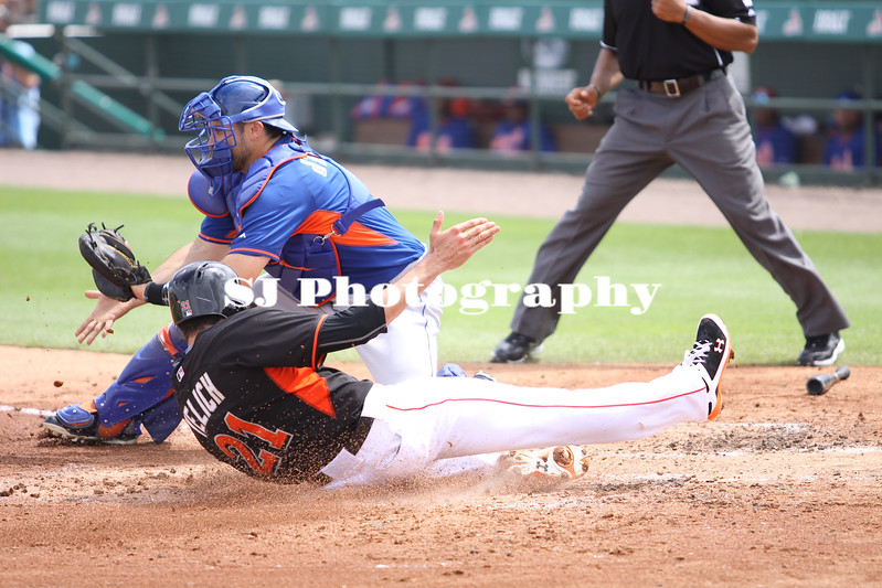 Christian Yelich of the Miami Marlis slides into home plate while Travis D'Arnaud waits to get the ball