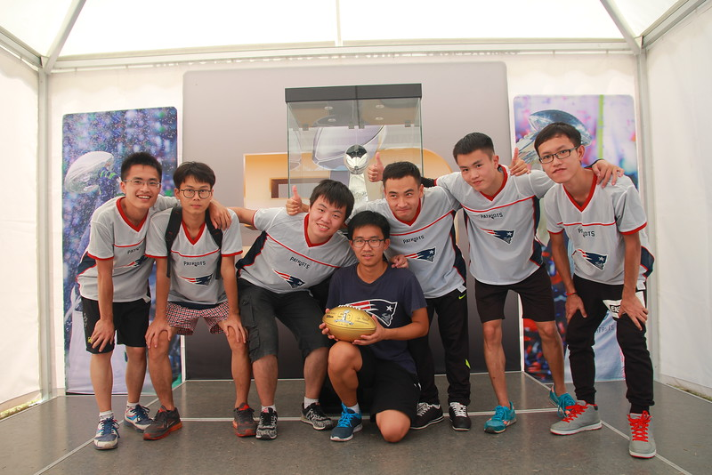 Wuhan University of Technology, Wuhan - NFL FLAG players get their photo taken with the Vince Lombardi Trophy and the commemorative Super Bowl 50 golden football during the NFL Super Bowl Truck stop in Wuhan.