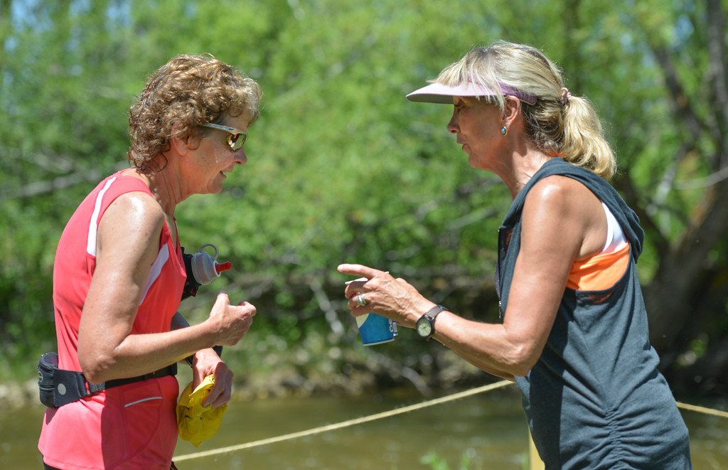 Justin Sheely | The Sheridan Press<br /> 18-mile runner Linda Schwamb of Sheridan, left, receives water from volunteer Tanna jones after crossing the finish line during the Bighorn Mountain Wild and Scenic trail run Saturday at Scott Park in Dayton.