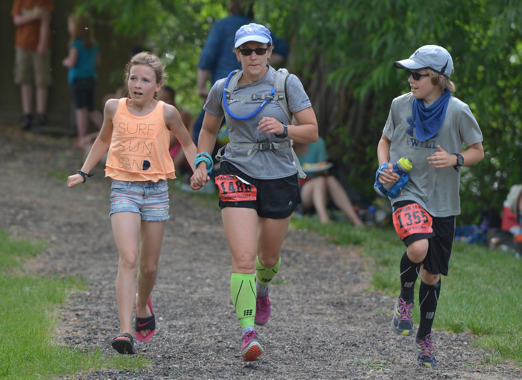 Justin Sheely | The Sheridan Press<br /> Eleven-year-old Kassidy Sollars, left, escorts her family Rhonda Sollars, and Jack Sollars, 13, of Billings, Montana, to the finish line during the Bighorn Mountain Wild and Scenic trail run Saturday at Scott Park in Dayton.