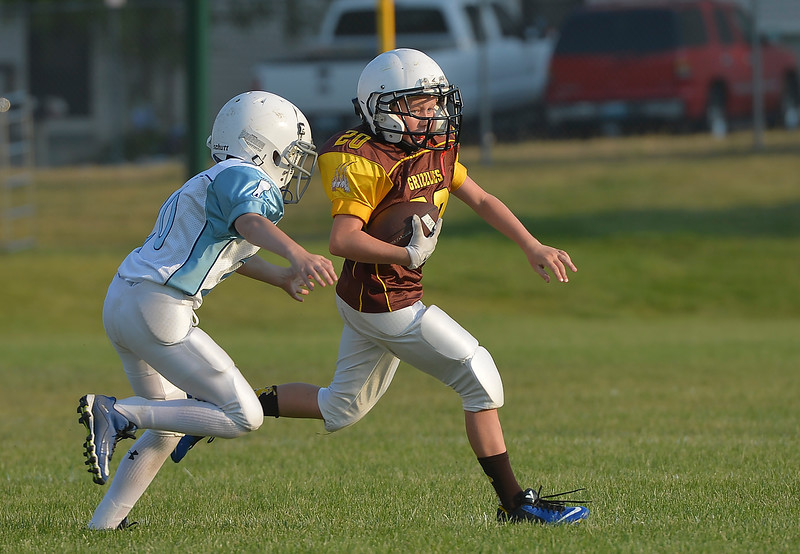 Justin Sheely | The Sheridan Press<br /> Tar Heels' Tanner Green, left, moves in to tackle Big Horn Grizzlies' Drew Heermann during 5th and 6th grade Little Guy Football Tuesday at Dan Madia Field. Sheridan's Tar Heels won 28-6.