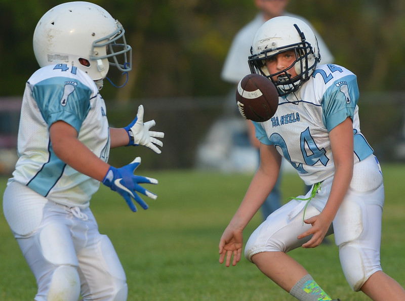 Justin Sheely | The Sheridan Press<br /> Tar Heels' Casen Wilson hands off the ball to Kolin Custis as they drive against the Big Horn Grizzlies during 5th and 6th grade Little Guy Football Tuesday at Dan Madia Field. Sheridan's Tar Heels won 28-6.