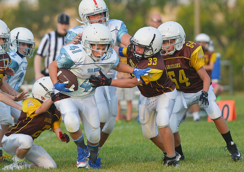 Justin Sheely | The Sheridan Press<br /> Tar Heels' Kolin Custis is tackled by Big Horn Grizzlies Cooper Garber (33) and Riley Green (64) during 5th and 6th grade Little Guy Football Tuesday at Dan Madia Field. Sheridan's Tar Heels won 28-6.