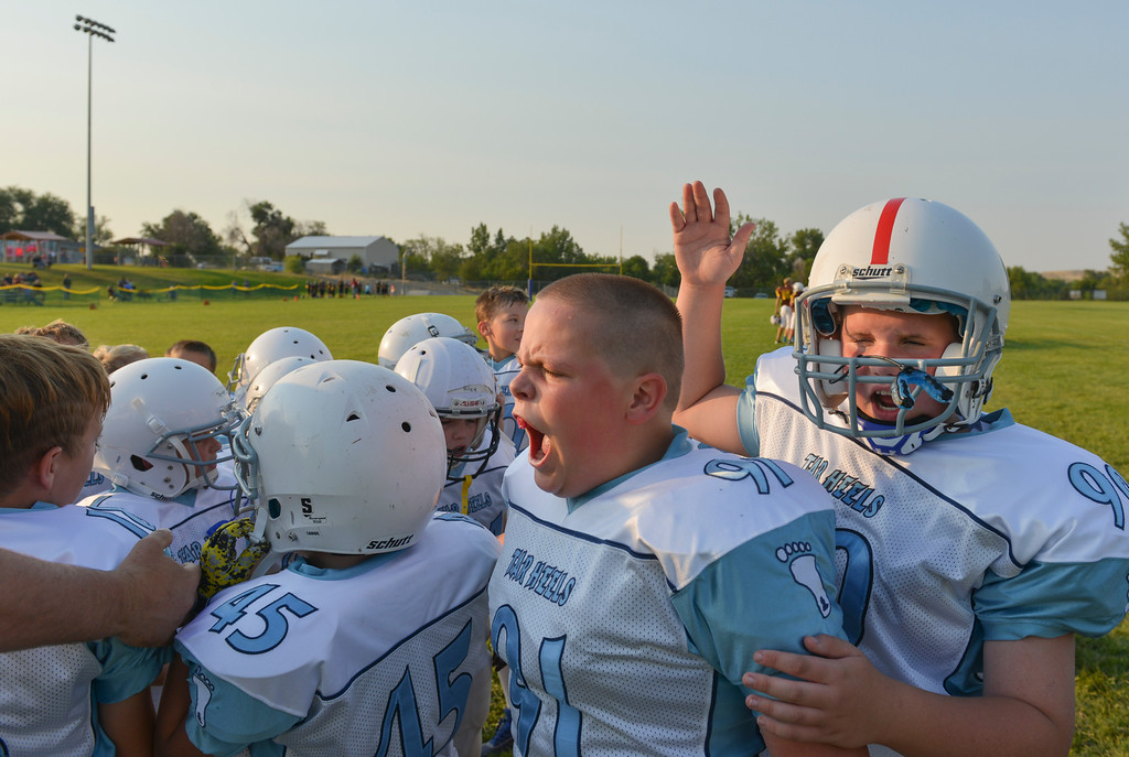 Justin Sheely | The Sheridan Press<br /> Tar Heels' Deedan Kirschner, left, and John Henry Justice get fired up during halftime before returning to take on the Big Horn Grizzlies during 5th and 6th grade Little Guy Football Tuesday at Dan Madia Field. Sheridan's Tar Heels won 28-6.