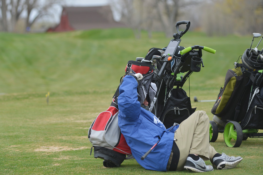 Justin Sheely | The Sheridan Press<br /> A student tries to shelter himself from the cold and wind as he waits for the group ahead to move out of driving range during the high school golf tournament Saturday at the Powderhorn golf course in Big Horn.