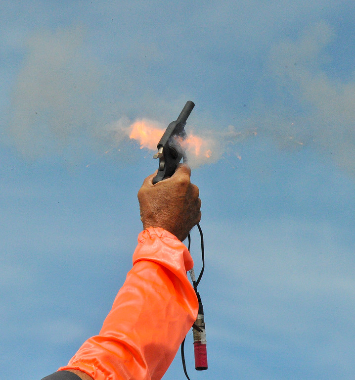 An official fires the starter pistol at the Dan Hansen track and field Invite in April. Mike Dunn | The Sheridan Press.