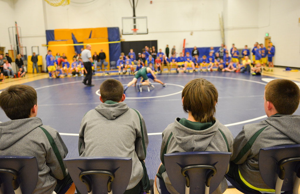 Justin Sheely | The Sheridan Press<br /> Tongue River Middle School wrestlers watch as their teammate wrestles during the wrestling meet Tuesday night at Sheridan Junior High School.