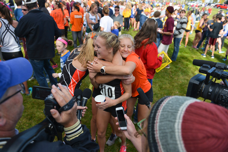 Justin Sheely | The Sheridan Press<br /> Jackson High School's Anna Gibson is congratulated by her teammates during an interview with the media in the class 4A girls State Cross-Country Championship Saturday at the Veterans Affairs Medical Campus in Sheridan. Gibson finished first 17:35.20.