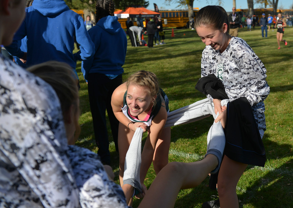 Justin Sheely | The Sheridan Press<br /> Kelly Walsh High School runners Skyler Sheffield, left, and Julia Burrows pull off a pair of stubborn sweatpants from a teammate during the State Cross-Country Championship Saturday at the Veterans Affairs Medical Campus in Sheridan.