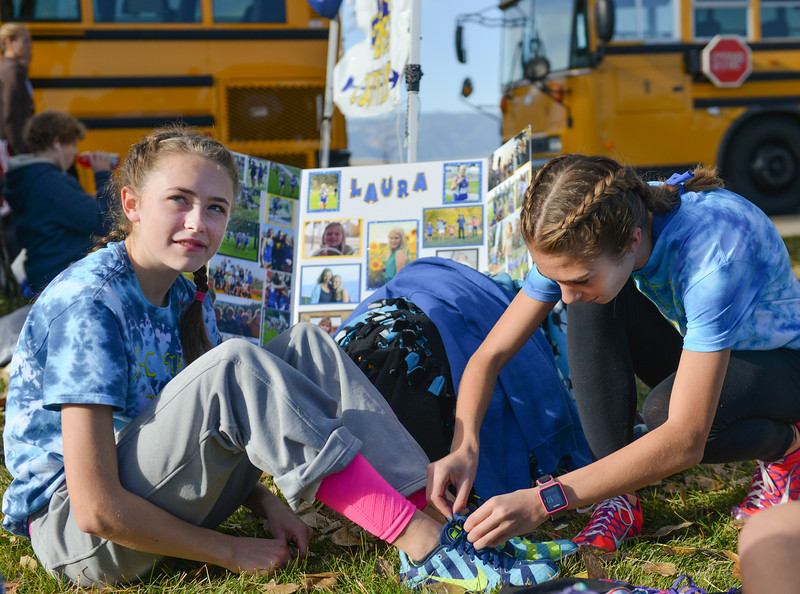 Justin Sheely | The Sheridan Press<br /> Sylvia Brown, left, sits as as McKinley Christopherson ties her shoes during the State Cross-Country Championship Saturday at the Veterans Affairs Medical Campus in Sheridan.