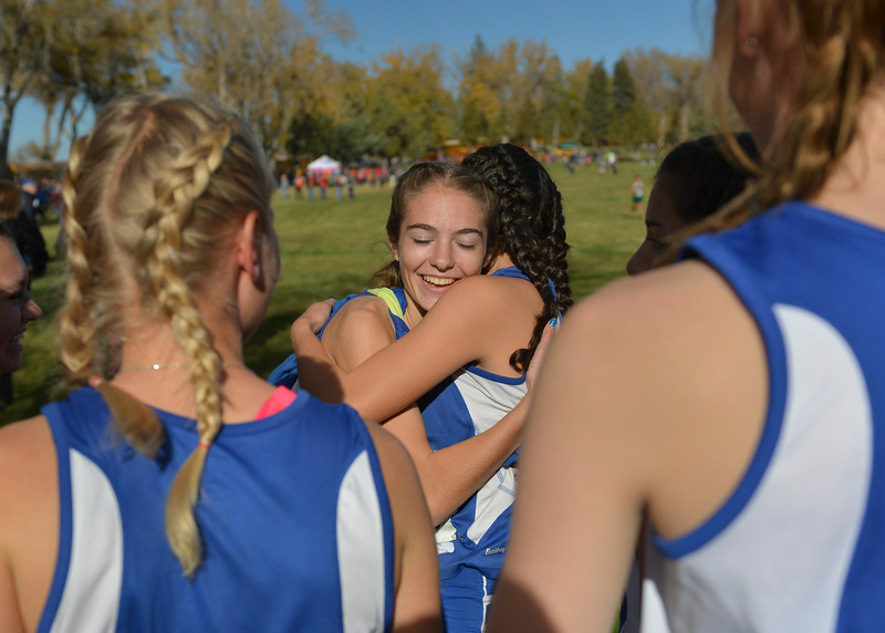 Justin Sheely | The Sheridan Press<br /> Sheridan's McKinley Christopherson embraces her teammates prior to competing in the class 4A girls State Cross-Country Championship Saturday at the Veterans Affairs Medical Campus in Sheridan.
