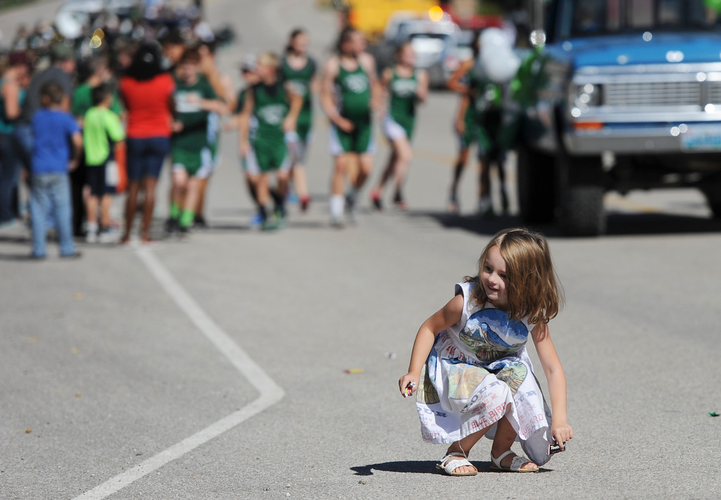 Justin Sheely | The Sheridan Press<br /> Five-year-old Keira Cooper picks up candy during the Tongue River High School Homecoming Parade on Friday in Dayton.