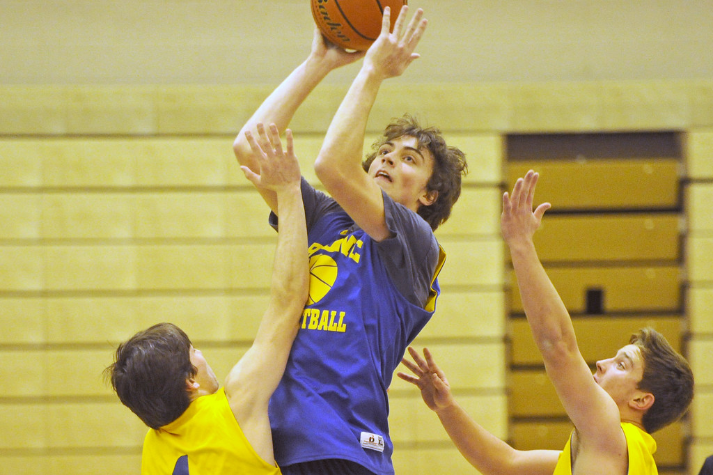 Aaron Woodward, center, shoots a floater over a pair of defenders during practice on Wednesday, Dec. 7 at Sheridan High School. Mike Pruden | The Sheridan Press