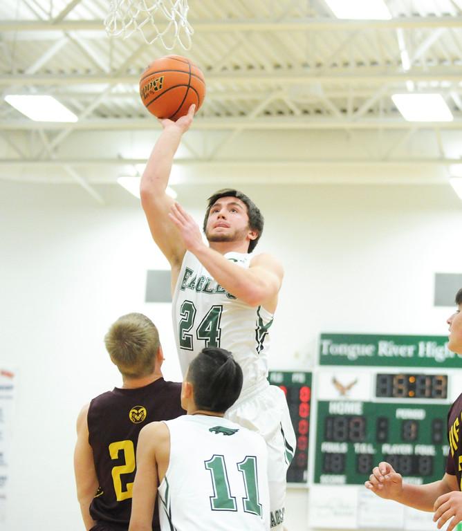 Dylan Lyons, top, jumps up for a layup Friday night at Tongue River High School. Mike Dunn | The Sheridan Press.