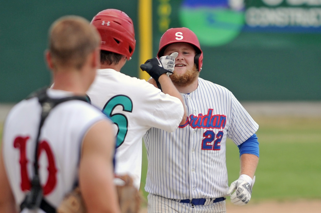 Kris Clark, right, bumps knuckles with Bryan Martini after Clark blasted a home run over the left field fence during the Troopers alumni game on Saturday, July 16 at Thorne-Rider Stadium. Clark and the alumni won the game 21-6. Mike Pruden | The Sheridan Press