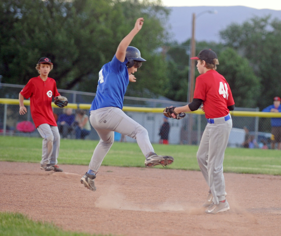 Dax Sargent, center, attempts to dodge a tag while running to second base during the Little League minor league championship on Monday, July 11 at Oatts Fields.