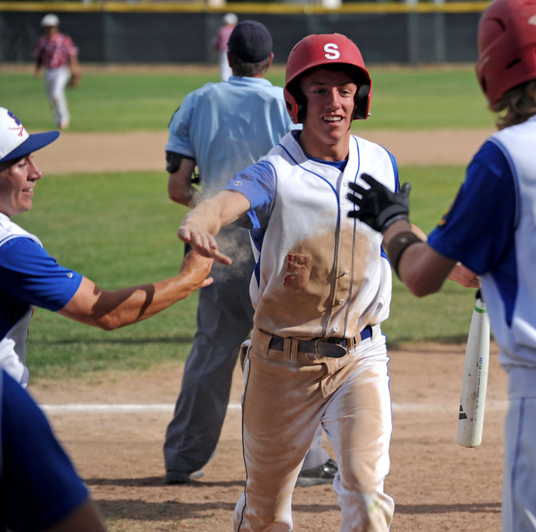 Jeffrey Shanor, center, receives congratulations from his teammates after diving safely into home plate during the Troopers' doubleheader against Gillette on Tuesday, July 5 at Thorne-Rider Stadium. Mike Pruden | The Sheridan Press