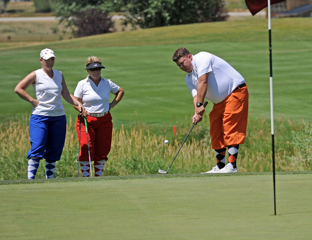 Angela Simmons, left, and Teresa Dewald, center, look on as Dustin Dewald chips a shot onto the green during the Sheridan Memorial Hospital Tournament on Friday, July 8 at the Powder Horn. Mike Pruden | The Sheridan Press