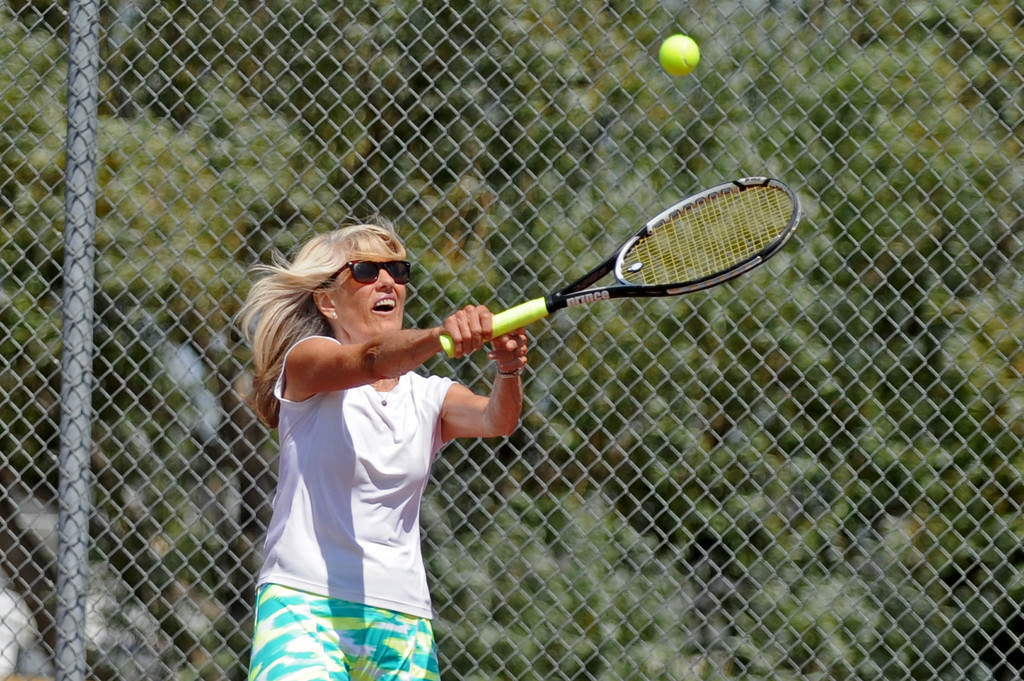 Lorna Brooks returns a high shot during the mixed doubles tennis tournament at the Wyoming Senior Olympics on Saturday, August 6 at the Sheridan High School tennis courts. Mike Pruden | The Sheridan Press