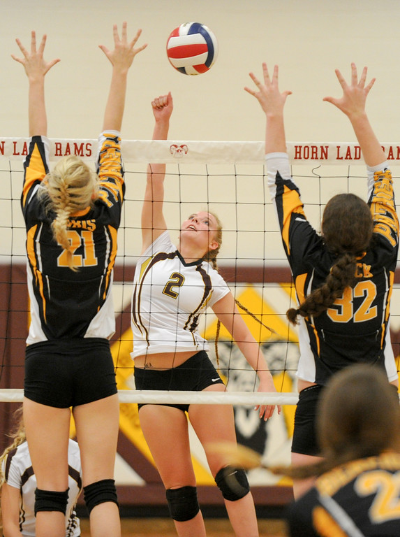 Mike Dunn | The Sheridan Press. <br /> Emily Blaney, middle, tips the ball over the net Saturday against Wright.