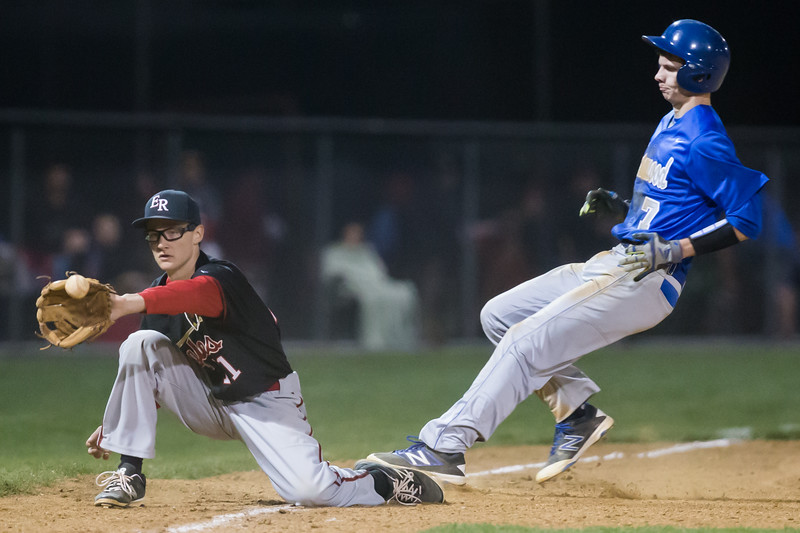 ERHS' Jayson Cross attempts to get out SHS' Cameron Irvine on third base.