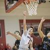 Logan Comer goes in for a layup against Luke Estep and Vincent Jimenez