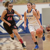 Addison DeLucas brings the ball down court being pursued by Naomi Gibson