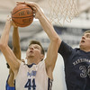 Joel McKay takes a kump shot under the basket against Harrisonburg's Danny Dombrowski and Madison's Dre Twyman