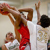 Javon Butler powers his way up for a shot against Zay Brown and #30