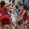 MacKenzie Freeze looks to pass the ball as a tro of Patriots close in