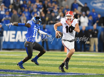 Georgia quarterback, Jacob Eason eludes Kentucky's J.D. Harmon on Saturday evening.  MARTY CONLEY/ FOR THE DAILY INDEPENDENT