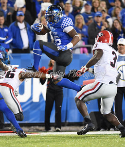 Kentucky's Benny Snell Jr. leaps over Georgia's Tyrique McGhee on Saturday evening.  MARTY CONLEY/ FOR THE DAILY INDEPENDENT