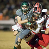 Wilson's Kyle Coombe is dragged down by ERHS' Darrias Brown and Chandler Breeden