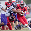 ERHS' Jwan Evans runs the ball as Strasburg's Tyjone Carter comes in for the tackle.