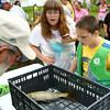 10-year-old Aaron Jacobs (right) and his grandmother Brenda Edmonds peer into the basket to see how much Jacobs' fish weighs at the Kids Fishing Clinic at the Kokomo Reservoir on Saturday, July 30, 2016.<br /> Kelly Lafferty Gerber | Kokomo Tribune