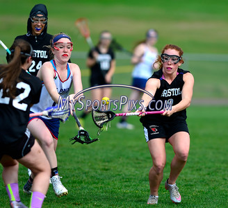 4/22/2016 Mike Orazzi | Staff Bristol Co-op girls lacrosse's Brianna Hamel (9) and and St. Paul Catholic High School's Morgan Moore (1) Friday afternoon in Bristol.