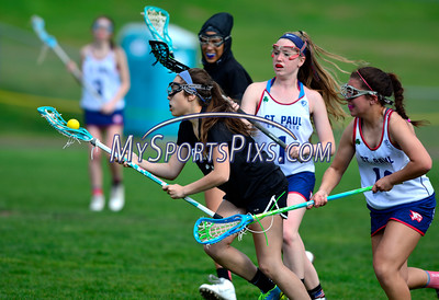 4/22/2016 Mike Orazzi | Staff Bristol Co-op girls lacrosse's Gabriele Abramczyk (23) and St. Paul Catholic High School's Morgan Moore (1) and Amethyst Peterson (16) Friday afternoon in Bristol.