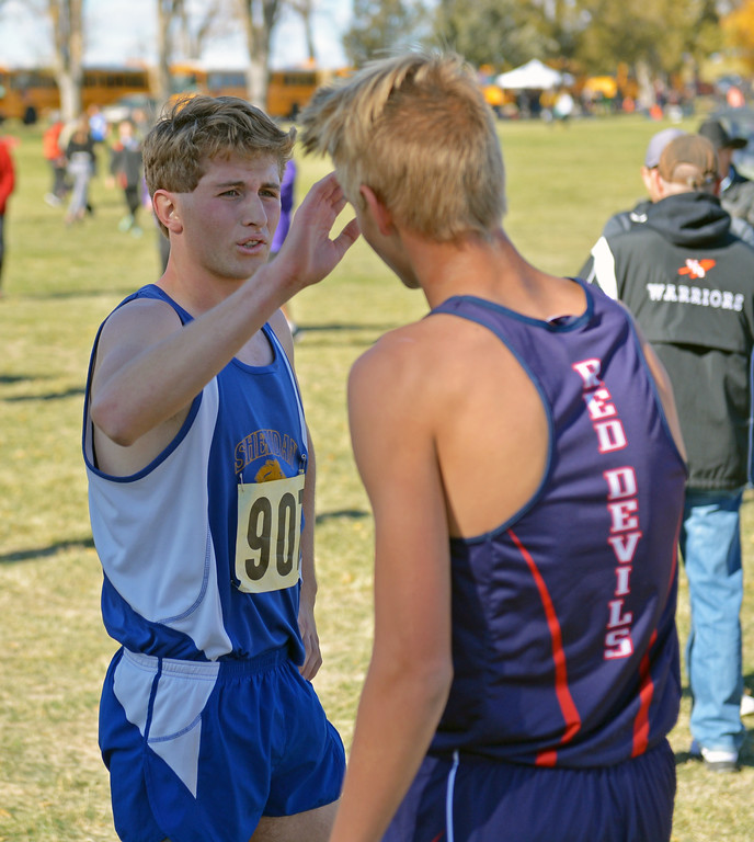 Sheridan's Brian Gonda high fives an Evanston opponent after crossing the finish line at the state cross-country meet on Saturday, Oct. 21 at the Veteran Affairs Medical Central in Sheridan. Mike Pruden | The Sheridan Press