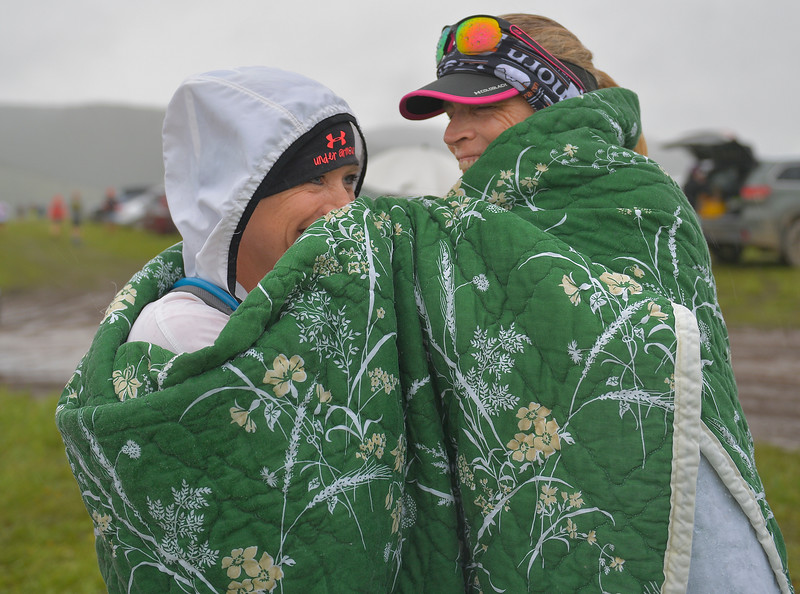 Justin Sheely | The Sheridan Press<br /> Meghann Boggs, left, and Nancy Yarborough of Douglas, Wyoming, seek warmth under a blanket prior to the start of the 32-mile race during the 25th annual Bighorn Mountain Wild and Scenic Trail Run Saturday at the Dry Fork aid station. Cold rain and wind brought a soggy start to Saturday's events.