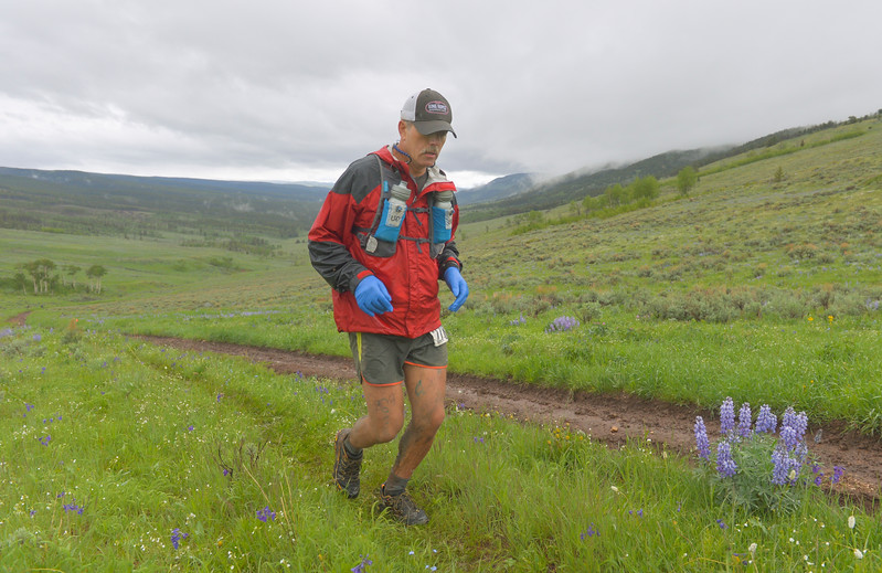 Justin Sheely   The Sheridan Press<br /> 100-mile runner Kelly Lance of Pocatello, Idaho, trudges up the hill during the 25th annual Bighorn Mountain Wild and Scenic Trail Run Saturday at the Dry Fork aid station. Cold rain and wind brought a soggy start to Saturday's events. Lance finished in 8th place.